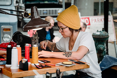 A woman attending Van Haven in Georgetown creates custom patches for sale with her old sewing machine.