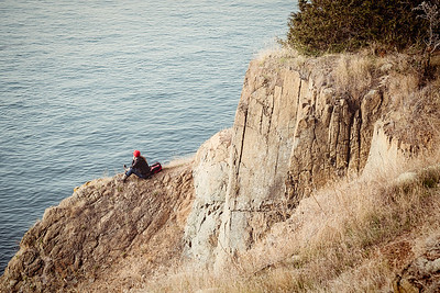 A young woman stares out over the ocean from cliffside on Lopez Island.