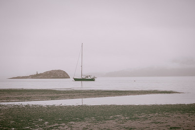 A sailboat, floats quietly while moored offshore on an overcast, foggy morning at Spencer Spit State Park.
