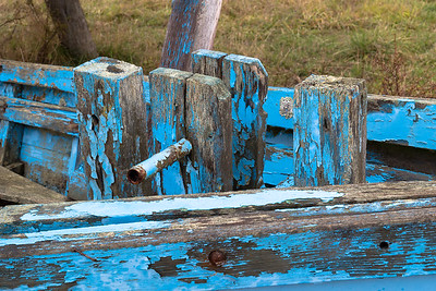 Blue, peeling paint on an old boat once used to fish for salmon.