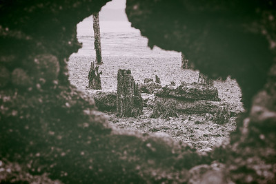 Old pilings and rocks seen through a hole in a stone wall, part of an old dock,