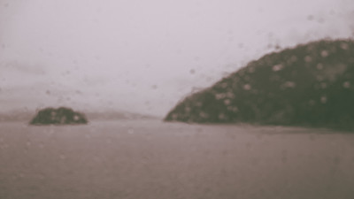 A blurry and foggy outside seen through a rain-dabbled ferry window.