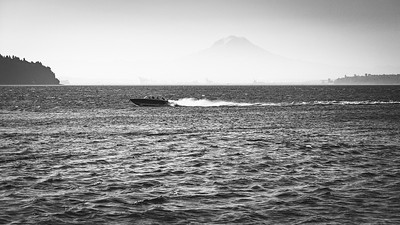 View from Sunrise Beach Park with a speedboat racing by with Mt. Rainier in the Background.