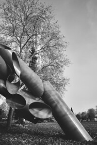 Alexander Liberman's largest sculpture, Olympic Iliad, (1984) with a fog-shrouded Spaced Needle behind a large tree in the background.