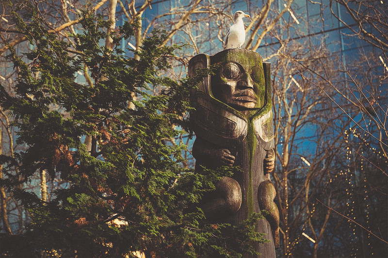 Totem pole carving with a seagull resting on top in Occidental Square, Seattle.