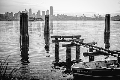 A cargo ship is framed by groupings of pilings with a seagull on one, a small boat is moored in the foreground.