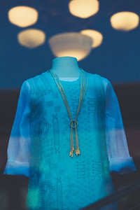 A gold-colored necklace adorns a woman's knitted, blue top on a headless mannequin with glowing orbs of light in the background.  Seen in Fairhaven, WA.