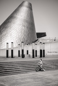 A young boy rides below the steps to The Glass Museum in Tacoma, Washington.