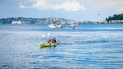 A man and woman paddle a kayak on the water in front of Alki where SubPop Records held a 30th anniversary celebration.