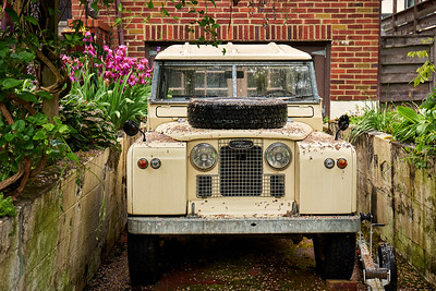 Old Land Rover parked in the driveway of a home in West Seattle.
