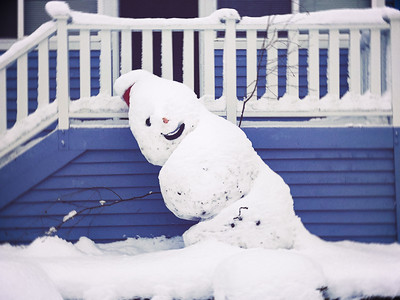 snowman;melting;falling;winter;porch;snow;railing;house;blue