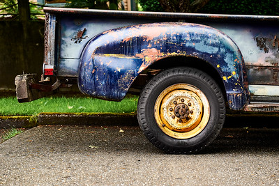 Rear quarter panel of an old truck with a wooden bumper.