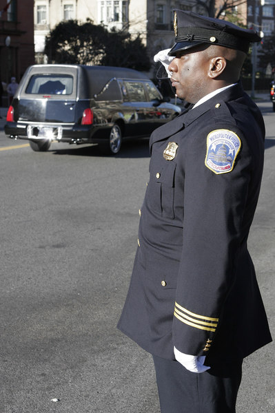Officer M.B. Suber of the Metropolitan Police Department salutes the flag draped coffin of President Gerald Ford as it turns onto Massachusets Avenue, Washington, DC