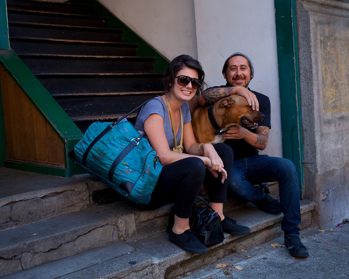 Couple with their dog sitting on the steps of their apartment