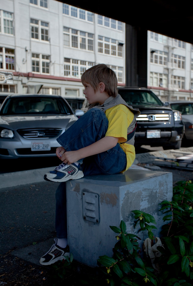 Boy sitting on an electrical box under the highway 99 viaduct tying his shoe