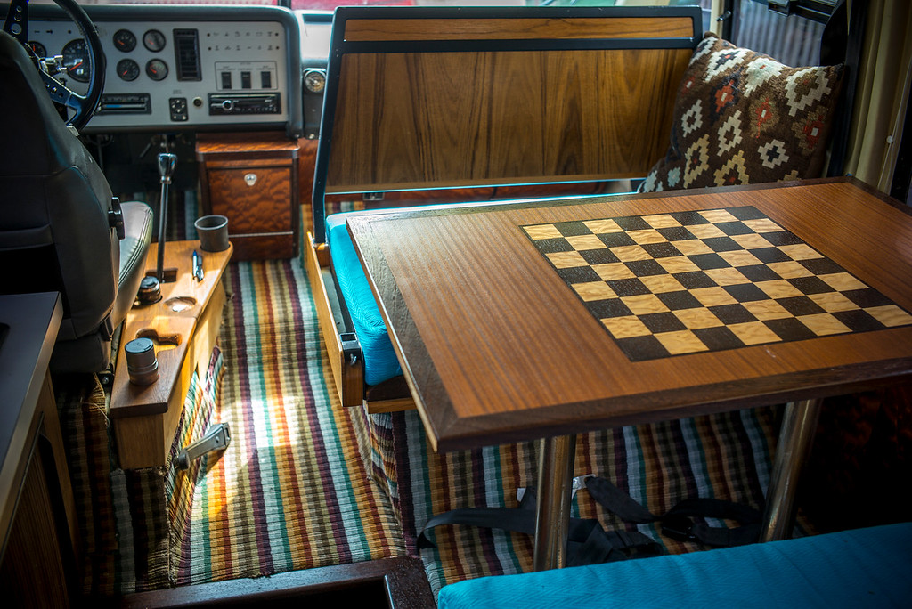 I've had much of the interior rebuilt, using fine woods (teak, sapele, and wenge) as well as fabrics and carpeting by Missoni Home. The front passenger seat back flips over to face forward while driving or backward to eat or play chess on the inlaid table. The teak side console has been carved out to accommodate my camera, lenses, pens, spare change, coffee cup, etc. The driver's seat is made by Ricaro. The 5 speed stick shift and powerful turbo allows for very sporty driving. While top speed supposedly is 100mph, I have never taken it past 87 but even at that speed, the ride is exceptionally smooth.<br /> The table drops down to form a bed for a third passenger as well (and a large bed in the back sleeps two.)