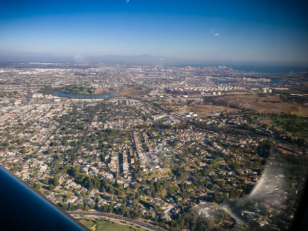 We're crossing over Rolling Hils Country Club (can just see Palos Verdes Drive E below and Palos Verdes Drive N ahead).  Mahado Lake, Terminal Island, and the L.A. Harbor are ahead.