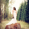 Beautiful bride standing outdoors on a hay bale