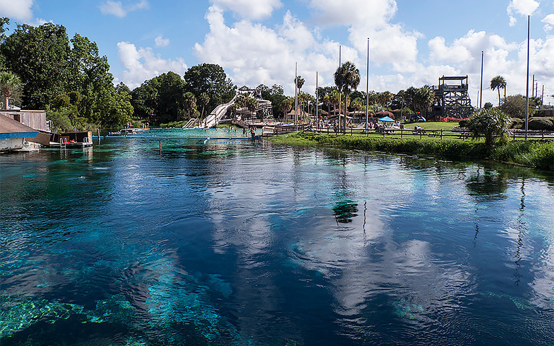 "Beautiful clear waters of Weeki Wachee Springs can be seen in the foreground. This view is looking across the water toward the ""Buccaneer Bay"" water park portion of Weeki Wachee."