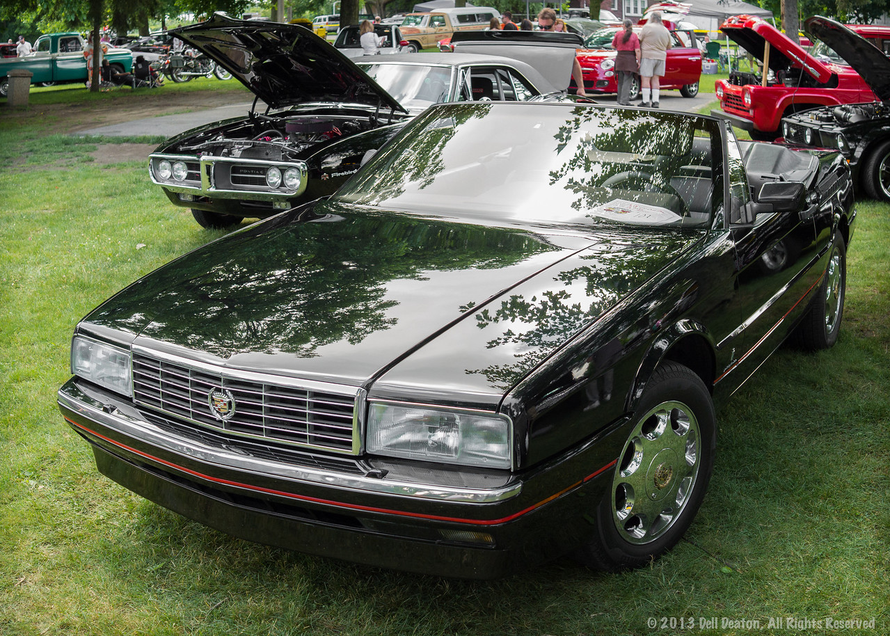 Black 1989 Cadillac Allanté, at 2013 Cinnamon's Annual Father's Day Car Show, held in conjunction with National Strawberry Festival. Site: Victory Park, Belleville, Michigan.  Photographed using Leica X2 digital camera with Elmarit 24mm f/2.8 lens; APS-C sensor (23.6mm x 15.8mm), 16.2 megapixels; set to f/5.0 at 1/250-second exposure, ISO 800; daylight. Composed for 7 x 5 aspect ratio; raw to jpeg. Processed in Adobe Lightroom 4.  Photographic equipment: Norman Camera, Kalamazoo, Michigan  June 16, 2013