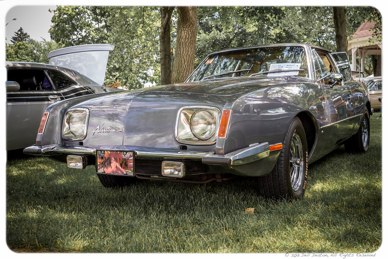"Definitely counted among ""Bond car"" photos I've taken. This 1977 Avanti II was shown in Belleville, Michigan, at the 2013 Cinnamon's Annual Father's Day Car Show, where it was voted ""best"" in an exotic vehicle category. The owner of this Avanti II, coincidentally, named Mr Bond. My interest is in its historic roots to the black 1963 Studebaker Avanti owned by James Bond author and creator Ian Fleming.  Photographed using Leica X2 digital camera with Elmarit 24mm f/2.8 lens; APS-C sensor (23.6mm x 15.8mm), 16.2 megapixels; set to f/5.0 at 1/400-second exposure, ISO 400; daylight. Composed for 7 x 5 aspect ratio; raw to jpeg. Processed in Adobe Lightroom 4.  Photographic equipment: Norman Camera, Kalamazoo, Michigan  June 16, 2013"