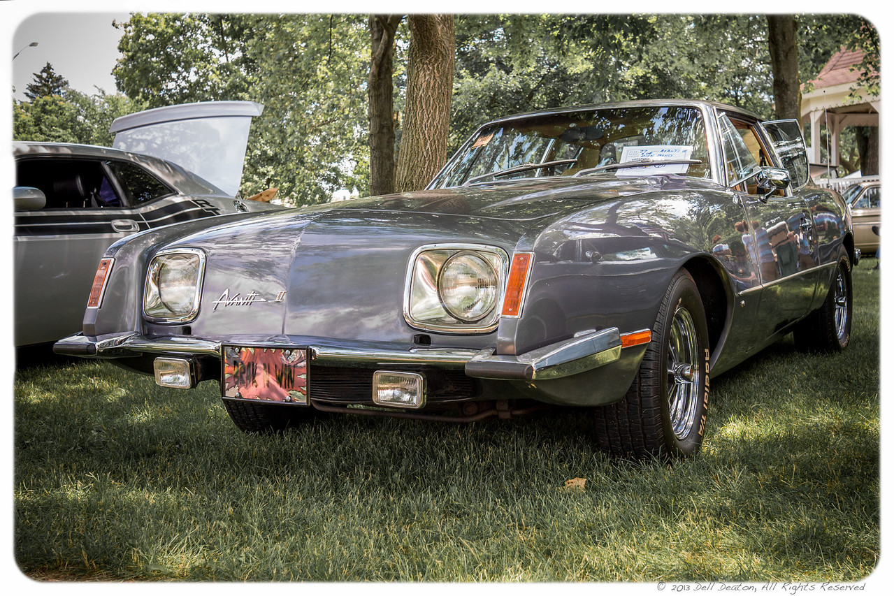 """Definitely counted among """"Bond car"""" photos I've taken. This 1977 Avanti II was shown in Belleville, Michigan, at the 2013 Cinnamon's Annual Father's Day Car Show, where it was voted """"best"""" in an exotic vehicle category. The owner of this Avanti II, coincidentally, named Mr Bond. My interest is in its historic roots to the black 1963 Studebaker Avanti owned by James Bond author and creator Ian Fleming.  Photographed using Leica X2 digital camera with Elmarit 24mm f/2.8 lens; APS-C sensor (23.6mm x 15.8mm), 16.2 megapixels; set to f/5.0 at 1/400-second exposure, ISO 400; daylight. Composed for 7 x 5 aspect ratio; raw to jpeg. Processed in Adobe Lightroom 4.  Photographic equipment: Norman Camera, Kalamazoo, Michigan  June 16, 2013"""