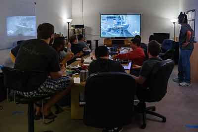 In the main conference room, someone plays Star Wars: Battlefront while the team feasts on pizza