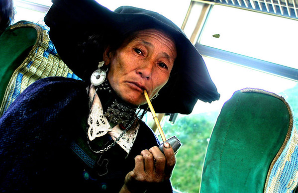 Yi bus rider. Meigu, China