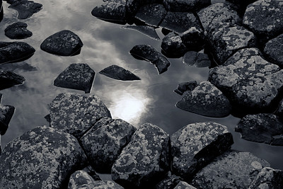 Sun through clouds with water and rocks