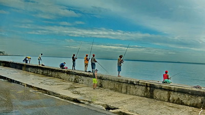 Fishermen on the 'Malecon', a broad walkway, roadway and seawall which stretches for 5 miles along the coast in Havana