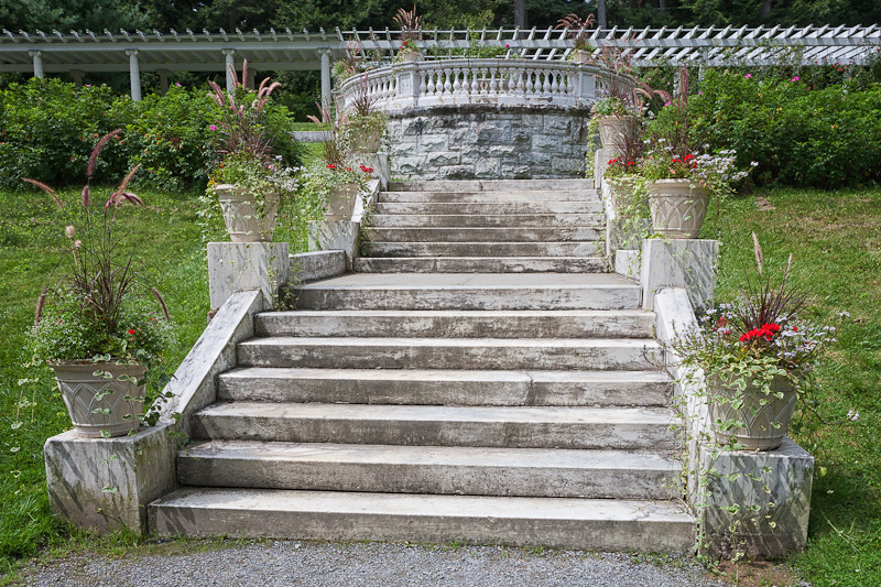Steps leading to the balcony and upper level pergola with large terracotta jardinières filled with geraniums.
