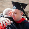 Dcn. William Burmester is congratulated by Fr. Denis Robinson, OSB, after graduation on May 13.
