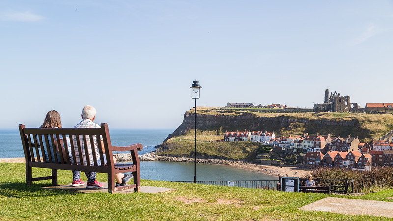 Couple on a bench overlooking Whitby harbour
