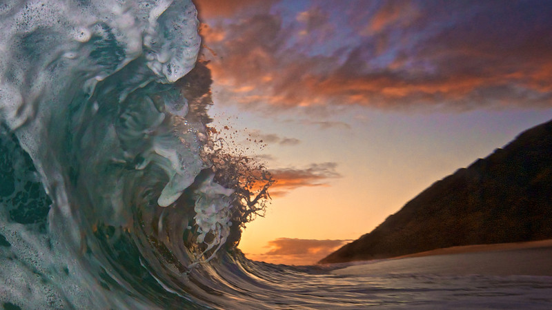 Warm sunset with a wave crashing on a secret beach.