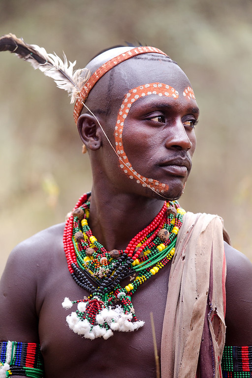 Hamar men pay a very special attention to face painting and hair. They use ostrich feathers as part of their hair dress which symbolizes hunting and the domain of nature. To protect the hairdo, men always carry a wooden headrests they use for pillows. This young fellow was about to get married, so the face is painted with the heart symbol.