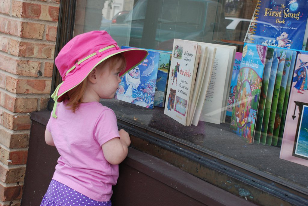 My 2 year old granddaughter eyeing some great reading through a storefront window.<br /> <br />  <br /> <br /> Taken with a Nikon D80<br /> <br /> Cyndy Luckey<br />   Woodstock, IL