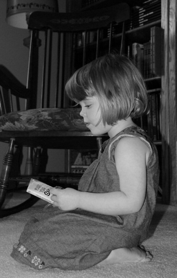 My three year old granddaughter loves to read, and I always find her in the corner of our living room lost in a good book.<br /> <br />  <br /> <br /> Taken with a Nikon D80<br /> <br /> Bob Luckey<br />   Woodstock, IL