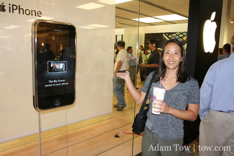 Rae stands next to the giant iPhone display.