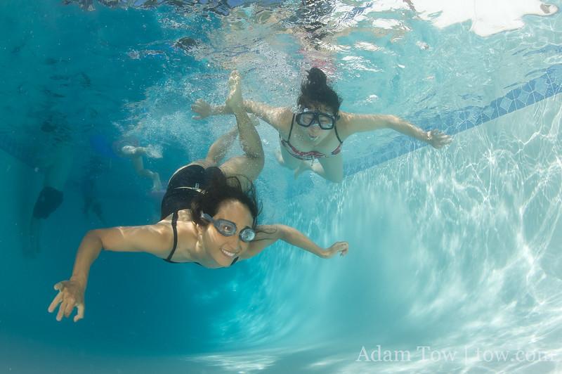 Rae and Petrice swim to the camera.