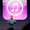 Phil Schiller in front of the iTunes Music Store logo.