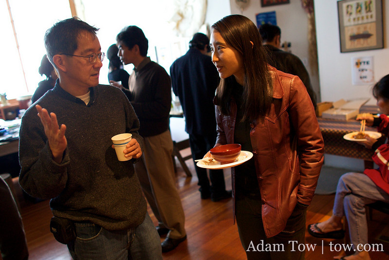 Rae speaks with photographer Bob Hsiang at Somei Yoshino's New Year's Day Open House in Oakland.
