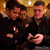 Chuck demos his iPhone application to John and Farid.