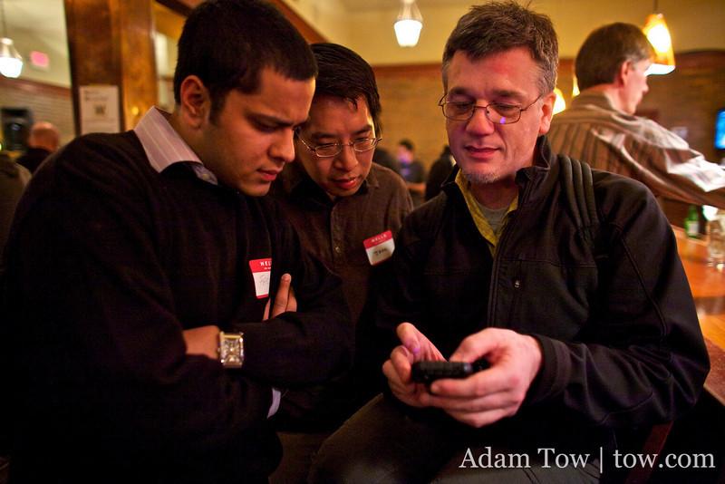 Chuck demos his iPhone application to John and Farid.