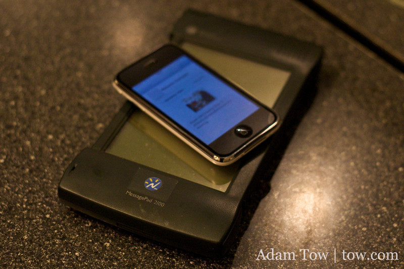 "The iPhone sits on top of the original Apple ""tablet,"" a Newton MessagePad 2100 with the Newton, Inc. logo."
