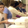 Kyle Horvath, 13, stacks up another meal to be boxed and shipped out into the community at Sacred Heart Church on Thanksgiving.<br /> Photo ben French