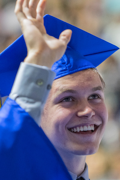 Bonneville High School graduate Corbin Shaw waves to his family in the crowd during the ceremony at the Dee Events Center in Ogden on May 22, 2017.