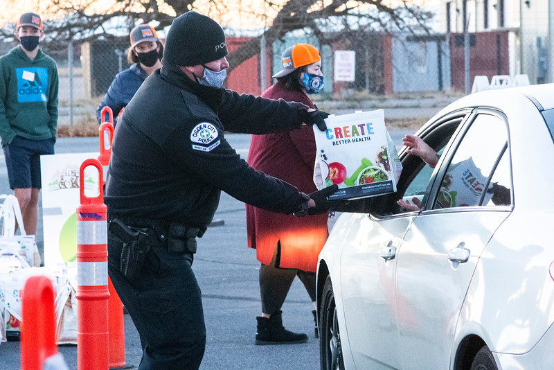 Officer Chris Bishop of the Weber County Sheriff's Office help donate food to families in need at the Weber County Fairgrounds in Ogden, on November 24, 2020.