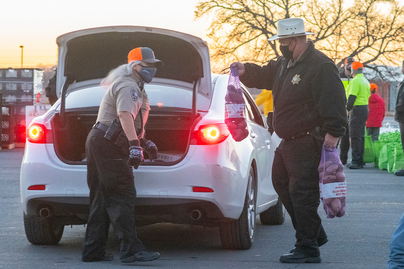 Norma Toschno and Scott johnson of the Weber County Sheriff's Office help donate food to families in need at the Weber County Fairgrounds in Ogden, on November 24, 2020.