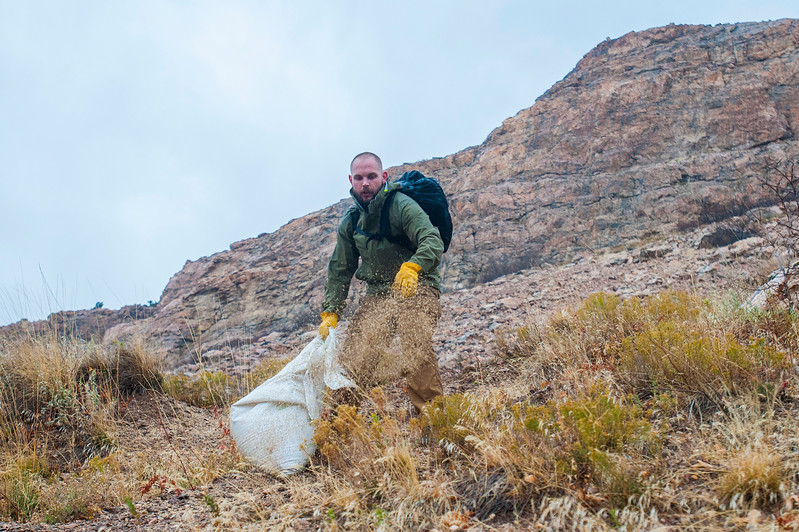 Volunteer Ethan White spreads seed on Saturday November 4, 2017, to prevent the Bonneville Shoreline Trail from eroding more than it already has. A big cause of the issue is hikers not staying on the designated path causing the hillside to wash away in the weather.
