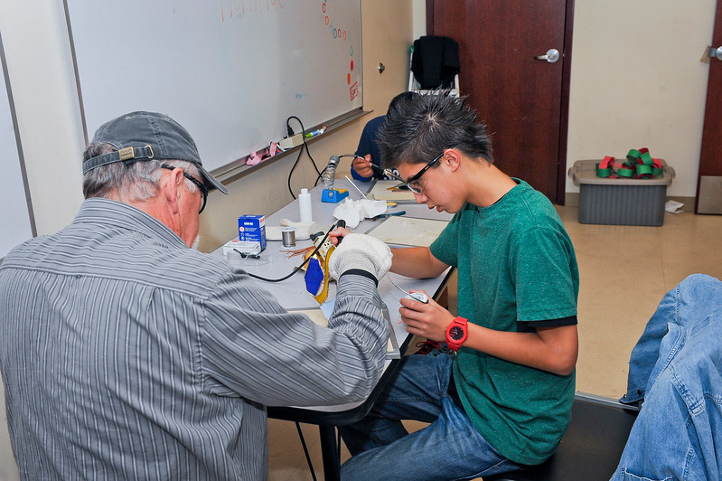 Kayden Freeland learns how to work with glass and make jewelry. Barbara and Terry Wesley are teaching the Boys and Girls Club students how to work with these different materials.  On December 12 2013.(Brian Wolfer Special to the Standard-Examiner)